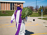 """05 APRIL 2020 - DES MOINES, IOWA:  Rev. RUSSELL LACKEY, left, follows """"Social Distancing"""" guidelines while he hands out palms during a drive through Palm Sunday service sponsored by Luther Memorial Church on the campus of Grand View University in Des Moines. About 150 people attended the service. They remained in their cars while the ministers read a short passage from the Bible, handed out palms and blessed them. On Sunday, 05 April, Iowa reported 868 confirmed cases of the Novel Coronavirus (SARS-CoV-2) and COVID-19. There have been 22 deaths attributed to COVID-19 in Iowa. Restaurants, bars, movie theaters, places that draw crowds are closed until 30 April. The Governor has not ordered """"shelter in place"""" but several Mayors, including the Mayor of Des Moines, have asked residents to stay in their homes for all but essential needs. People are being encouraged to practice """"social distancing"""" and many businesses are requiring or encouraging employees to telecommute.          PHOTO BY JACK KURTZ"""
