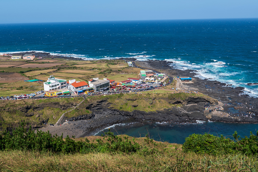 Numerous tourists visit the shops and explore the coastline at Black Sand Beach on Udo, an island off the coast of Jeju in Korea.