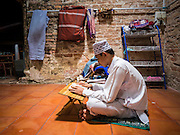 19 JUNE 2015 - PATTANI, PATTANI, THAILAND: A teenager reads the Koran in Krue Se Mosque during Ramadan services at Krue Se Mosque. Krue Se Mosque was started in 1583 but never completely finished. Ramadan is the ninth month of the Islamic calendar, and is observed by Muslims worldwide as a month of fasting to commemorate the first revelation of the Quran to Muhammad according to Islamic belief. This annual observance is regarded as one of the Five Pillars of Islam. Islam is the second largest religion in Thailand. Pattani, along with Narathiwat and Yala provinces, all on the Malaysian border, have a Muslim majority.             PHOTO BY JACK KURTZ