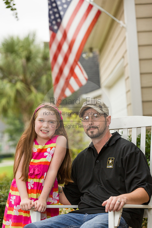 Rachel Mennet, a third-grader, poses with wounded warrior Nick Bailley September 23, 2014 in Summerville, South Carolina. Rachel led a successful fundraising effort using her lemonade stand to pay for training Abel to become a service dog for Nick.