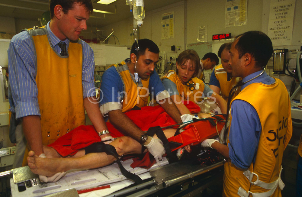 """At the Royal London Hospital, accident and emergency (A & E) medical staff wearing radiation-proof x-ray lead tunics very carefully move a patient to a more comfortable position after a road traffic accident in London. The patient is held firm in a splint after several fractures and his life hangs in the balance but he is the care of this team of five health professionals who give him the very best care. The Royal London Hospital is one of London's oldest, having been founded in 1740 and is a major teaching hospital in Whitechapel, East London. It is part of the Barts and the London NHS Trust, alongside St Bartholomew's Hospital (""""Barts""""), which is a couple of miles away."""
