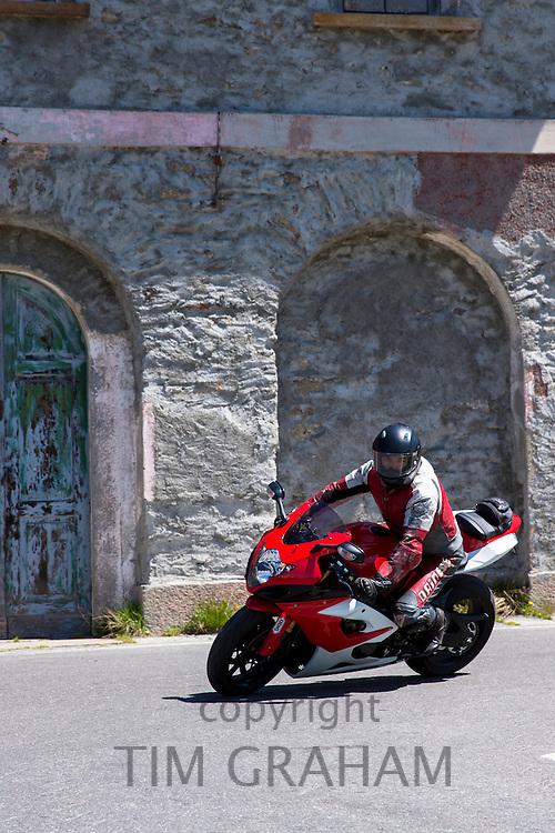 Motorcyclist on Honda motorbike drives The Stelvio Pass, Passo dello Stelvio, Stilfser Joch, to Bormio, Northern Italy