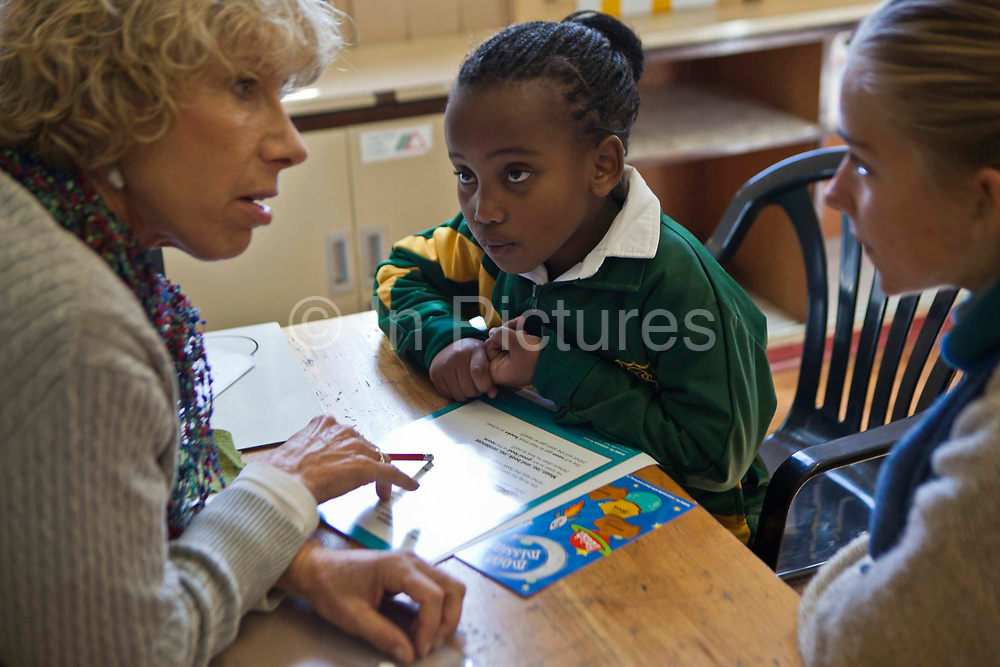 A young African school girl looks at her teacher as she discusses the exercise with a volunteer literacy teacher in a classroom in Observatory Primary School, Cape Town, South Africa. They sit at a desk and have reading sheets on the desk. The volunteer teachers have been provided to the school by Shine Centre which is a charity that aims to address the high illiteracy rate in South Africa by improving literacy levels among children in schools and disadvantaged communities.