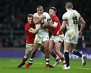 Jonathan Joseph of England is held up by Gareth Anscombe (l) and Steff Evans ® of Wales.England v Wales, NatWest 6 nations 2018 championship match at Twickenham Stadium in Middlesex, England on Saturday 10th February 2018.<br /> pic by Andrew Orchard, Andrew Orchard sports photography