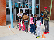 22 APRIL 2020 - DES MOINES, IOWA: Students and their parents wait for computers for distance learning to be distributed at Edmunds Elementary School. Schools in Iowa are closed for the rest of the school year because of the COVID-19 (Coronavirus/SAR-CoV-2) pandemic. Des Moines Public Schools expanded their school lunch and distance learning efforts this week. Lunches are being distributed at all of the district's elementary and middle schools and officials have started distributing computers so students can participate in distance learning.           PHOTO BY JACK KURTZ