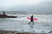 Jaimie Lee Mitchell heads into a high surf on Sunday, Nov. 1, 2020 at Rotary Beach Park in Ketchikan, Alaska.