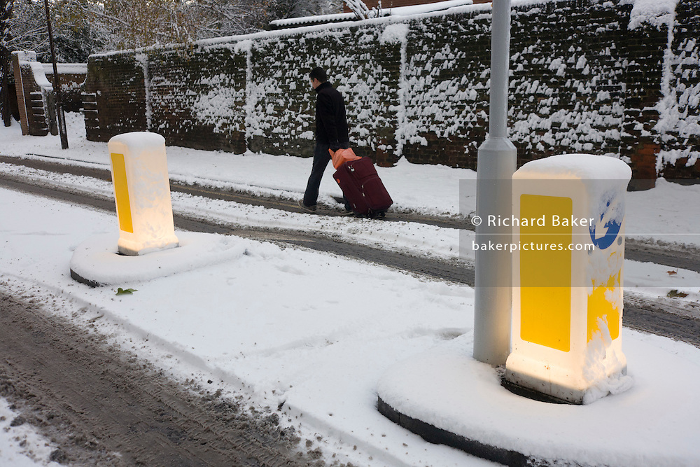 Illuminated road bollards and struggling traveller during wintry snows in south London.