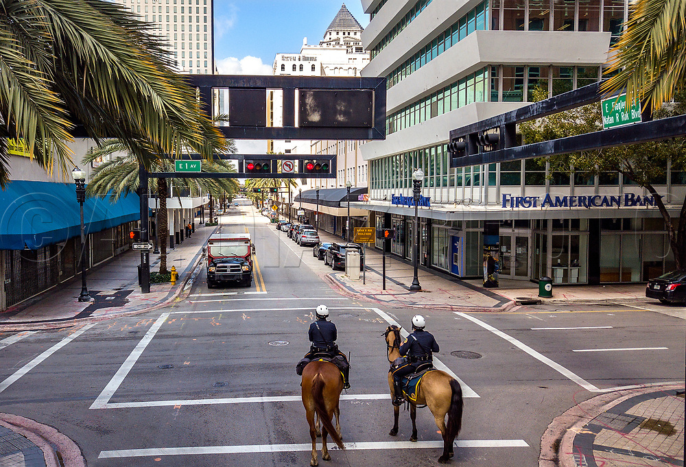City of Miami Mounted Patrol Officers Loisel Cruz riding Ike, at left, and Ruben Gonzalez riding Cody, at right, patrol along a quite and mostly shuttered Flagler Street due to the threat of COVID19 pandemic in downtown Miami on Wednesday, April 1, 2020.