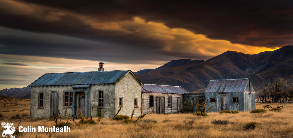 Dawn lights up cloudscape over historic (1939) farm buildings,  near St Bathans, Central Otago, New Zealand.