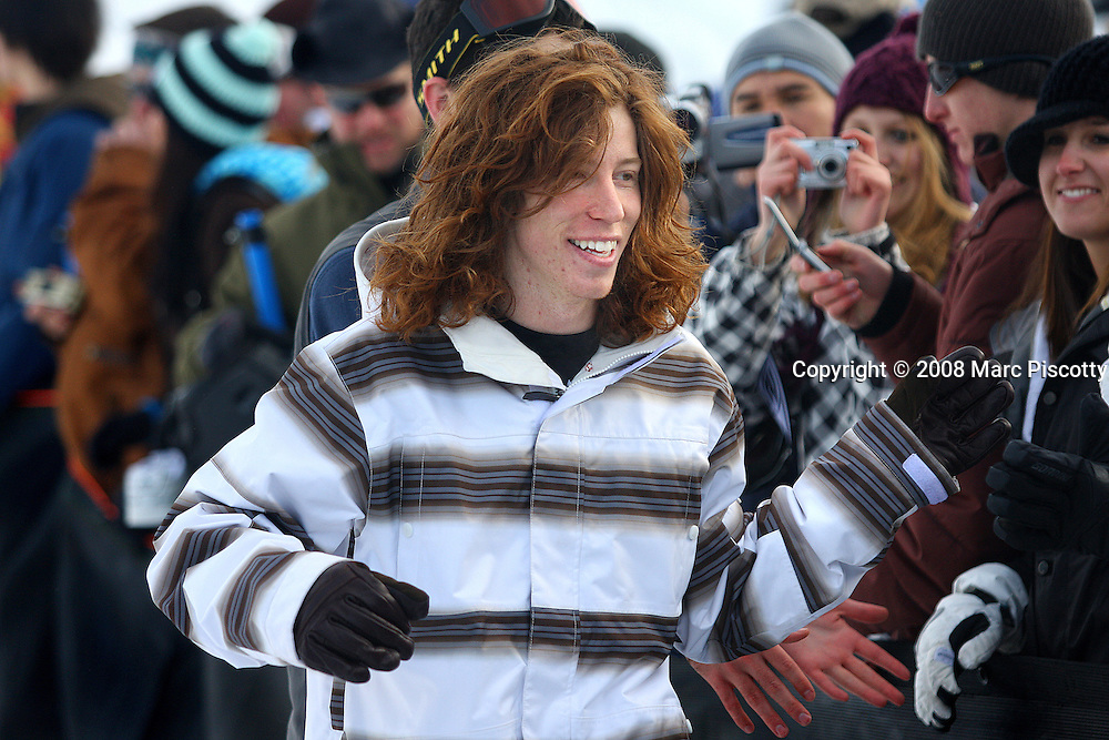 """SHOT 1/26/08 4:12:21 PM - Snowboarder Shaun White high fives fans as he signs autographs while walking towards the podium to accept a bronze medal in the Snowbaord Slopestyle event Saturday January 26, 2008 at Winter X Games Twelve in Aspen, Co. at Buttermilk Mountain. White finished third (83.33) behind Kevin Pearce (88.33) and Andreas Wiig (92.00). White did however win the Supeprpipe competition continuing his dominance in Winter X Games. The 12th annual winter action sports competition features athletes from across the globe competing for medals and prize money is skiing, snowboarding and snowmobile. Numerous events were broadcast live and seen in more than 120 countries. The event will remain in Aspen, Co. through 2010.Shaun Roger White (born September 3, 1986 in Carlsbad, California) is an American athlete. He has been a notable competitor in professional snowboarding since he was fourteen years old, but is also known for his skateboarding. He is known for his shock of red hair, for which he has become known as """"The Flying Tomato"""". White gained sponsorship from Burton after his mother phoned them to see if they had a board small enough for her 6-year-old son..(Photo by Marc Piscotty / © 2008)"""