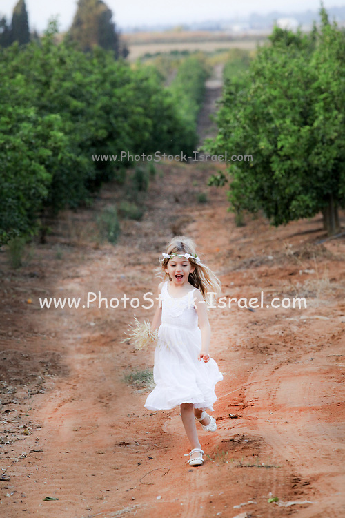 Young girl of six, in white dress and a wreath of flowers on her head runs in an orchard
