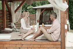 Couple chic sitting garden drinking cocktail happy