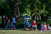 Mothers attempt to social distance while letting their children play closely and share food, demonstrating confusion over the rules  - People enjoy the sun on Clapham Common after the Government eased restrictions and allowed people to meet - Lambeth Council have replaced signs to say stay alert and to allow people sit on benches. The eased 'lockdown' continues for the Coronavirus (Covid 19) outbreak in London.