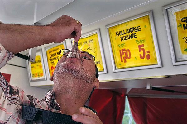 Nederland, Doetinchem, 25-5-2005Klanten bij een viskar uit Spakenburg kopen onder andere hollandse nieuwe haring. De meeste vis wordt gevangen in de zee bij Noorwegen door Noorse vissers. Visvangst, visquotum, vangstquotum, visstand, voeding, traditie, gezondheid, voedsel, prijs, prijzen. Visserij, overbevissing.Foto: Flip Franssen/Hollandse Hoogte