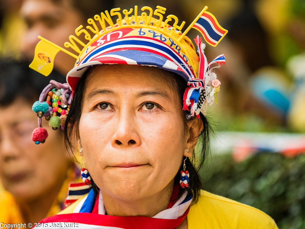 """05 DECEMBER 2015 - BANGKOK, THAILAND: A woman wears a """"long live the King"""" headband in the plaza at Siriraj Hospital on the 88th birthday of Bhumibol Adulyadej, the King of Thailand. Hundreds of people crowded into the plaza hoping to catch a glimpse of the revered Monarch. The King has lived at Siriraj Hospital off and on for more than four years.     PHOTO BY JACK KURTZ"""
