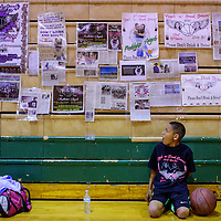 Kevin Martin sits by a display of news clippings and posters about the Peshlakai sisters on the sidelines of a charity basketball tournament in Newcomb Saturday.