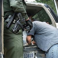 Verenigde Staten.Arizona.Nogales.juli 2005.<br /> Grenspolitie arresteert illegalen in de woestijn van Zuid Arizona, die illegaal vanuit Mexico de Verenigde Staten zijn binnengekomen. Ze worden gefoullerd op wapens en hun papieren worden gecontroleerd. Daarna worden de illegalen naar het hoofdbureau van de grenspolitie getransporteerd, waarna ze geregistreerd worden alvorens ze terug de grens overgebracht worden.pistool.Border Patrol.Grensproblematiek.Illegale vluchteling.Mexicaan.Papier ondertekenen.Nummerplaat.Autoriteit.<br /> Op de foto ondertekent een gearresteerde illegaal een papier waarin wordt gezegd, dat hij vrijwillig terugkeert naar Mexico.<br /> Archives 2005. Chase by police on illegal Mexicans who cross the border in Arizona.