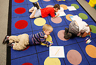 First grader Adam Kotzian does his writing work on the floor of his classroom at Eagleview Elementary school in Thornton, Colorado March 31, 2010.  Adam and his parents are achondroplasia dwarfs but his sister Avery is not.   REUTERS/Rick Wilking (UNITED STATES)