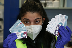 © Licensed to London News Pictures. 01/05/2021. London, UK. A volunteer holds Covid-19 vaccination record cards at a vaccination centre in Haringey, north London. In the UK, over 34.2 million people have received a first dose and almost 14.5 million are fully vaccinated. People aged 40 and over can now book their appointments through the national booking website as part of the next phase of the government's vaccination programme. <br /> <br /> ***Permission Granted*** <br /> <br /> Photo credit: Dinendra Haria/LNP