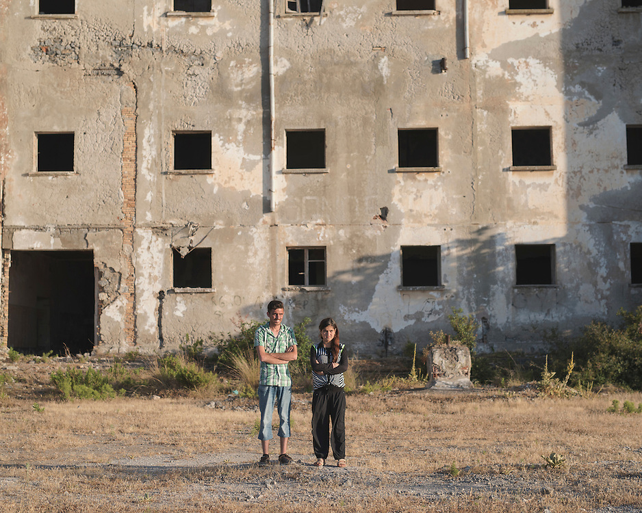 Yazidi refugees Hazim Elias Khadeda 22  and his sister Leena Elias Khadeda  16 photographed in front of the abandoned building of the Royal Technical School of Leros.<br /> <br /> This building was built in the 1930 by Fascist Italy as barack for the submarine crews stationed in the island. After WWII it  was turned into a a reeducation camp for the children of Greek Communists and into a technical school. From the mid 1950's until 1967 it was a technical school with boarding facilities. During the Colonel's Junta in Greece it was turned into a camp for members of the communist party. After the Junta it was abandoned and now it's about to collapse.