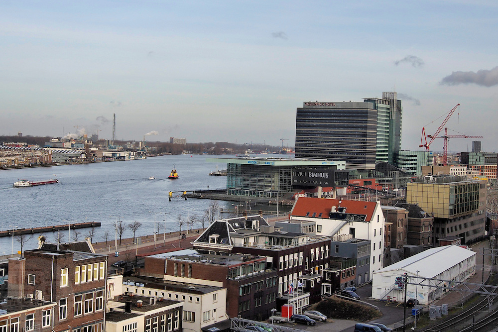 Het IJ in Amsterdam met het Muziekgebouw aan het IJ en het Mövenpick Hotel in de achtergrond.<br /> <br /> View over the IJ in Amsterdam with the Muziekgebouw aan het IJ and the Mövenpick Hotel.