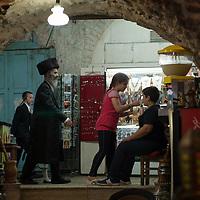 An orthodox Jewish man walks through the Old City of Jerusalem wearing a shtreimel hat, a traditional fur hat worn by Hassidic Jews on Shabbat and Jewish holidays.