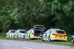 © Licensed to London News Pictures. 17/08/2021. Yarnton, UK. Police vehicles parked on the A40 in Yarnton in Oxfordshire following reports of a body being located in Cresswell Lake at approximately 20:30BST on Monday evening 16/08/2021. Thames Valley Police with the assistance of Oxfordshire Fire & Rescue Service and Hampshire Constabulary Marine Unit recovered the body of a woman from the water. The death is currently being treated as unexplained. Photo credit: Peter Manning/LNP