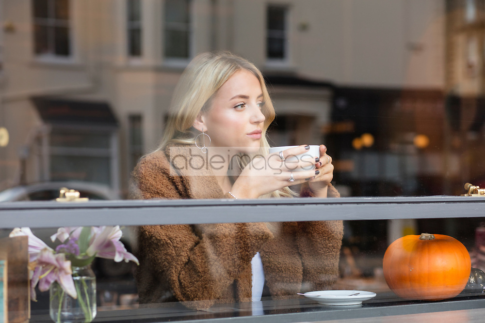 Young Woman Sitting in Cafe Having Coffee