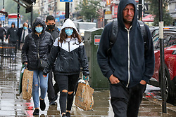 © Licensed to London News Pictures. 25/07/2021. London, UK.Shoppers are caught out in a heavy downpour in north London., after the recent heatwave.  According to The Met Office, torrential thunderstorms are expected in the capital. Photo credit: Dinendra Haria/LNP