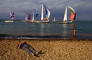A man sleeps on a shingle beach as a group of racing yachts slip past with sails blowing, during the Cowes racing regatta. As girl stands transfixed by the sudden boats' presence and stays in the surf, not venturing any further. But the man is unconscious and not even a fleet of racing yachts will wake him.