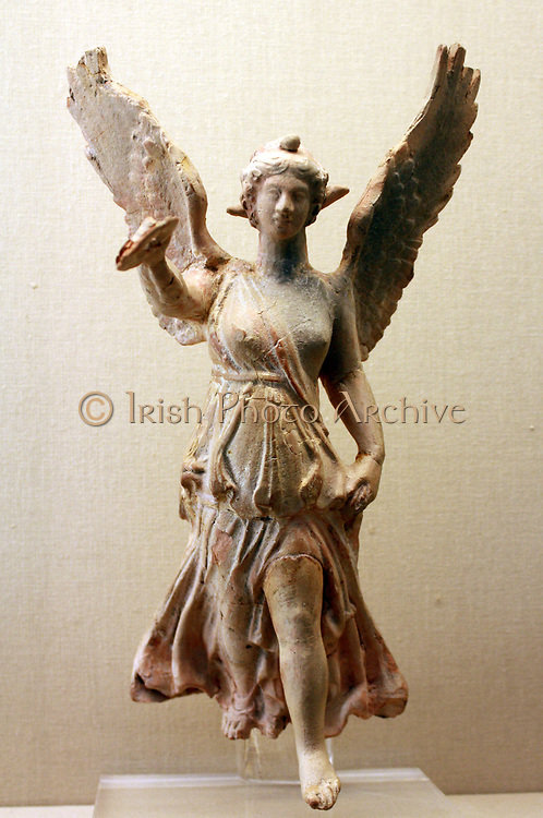Nike (goddess of Victory) about to land. This terracotta figure of Nike holds out a wreath for a victor. Her garment clings to her body, revealing the contours beneath but also billows out the enhance the sense of rapid movement. Made and found in Myrina, Turkey. About 50BC - AD 30.