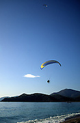 Motorised paraglider over the sea, Olu Deniz, Fethiye, Turkey