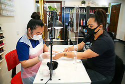 © Licensed to London News Pictures. 13/07/2020. London, UK. Nail beautician, HIEN THI THANH TRAN files KRISTINA'S nails in her salon in North London. Nail technicians and nail salons across the UK closed on 23 March following the coronavirus lockdown. As COVID-19 lockdown restrictions are eased, nail salons reopen today. Nail technicians and their clients are required to wear face coverings. Photo credit: Dinendra Haria/LNP