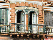 "An old building with balcony. In La Boca barrio (neighborhood) of Buenos Aires, tourists are attracted by colorful houses, the Caminito pedestrian street, La Ribera theatre, tango clubs, and Italian taverns. La Boca retains a strong European flavor, with many early settlers from Genoa, Italy. It sits at the mouth (""boca"" in Spanish) of the Matanza River (or Río Mataderos, or Riachuelo which simply means ?Creek?). La Boca is known among sports fans for La Bombonera stadium (Estadio Alberto J. Armando), home of Boca Juniors, one of the world's best known football (soccer) clubs. As a centre for radical politics, La Boca elected the first socialist member of the Argentine Congress (Alfredo Palacios in 1935) and hosted many demonstrations during the crisis of 2001 in Argentina, South America."