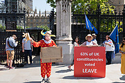 On the day Conservative MP Boris Johnson is announced as the new Prime Minister of the United Kingdom, a man dressed in a clowns outfit with a Boris Johnson mask campaigns outside Houses of Parliament on the 23rd July 2019 in the United Kingdom.