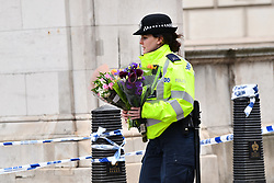 © Licensed to London News Pictures. 23/03/2017. London, UK. A police officer carrying flowers at the scene of the attack, the day after a lone terrorist killed 4 people and injured several more, in an attack using a car and a knife. The attacker managed to gain entry to the grounds of the Houses of Parliament, killing one police officer. Photo credit: Ben Cawthra/LNP