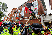 XR activist stands in a wooden tripod while being watched by the police as hundreds of fellow Extinction Rebellion climate protestors blocked Tufton Street, outside Tufton Court in central London on Wednesday, Sept 2, 2020. Over 90 people have been arrested so far as Extinction Rebellion protesters swarm central London. (VXP Photo/ Vudi Xhymshiti)