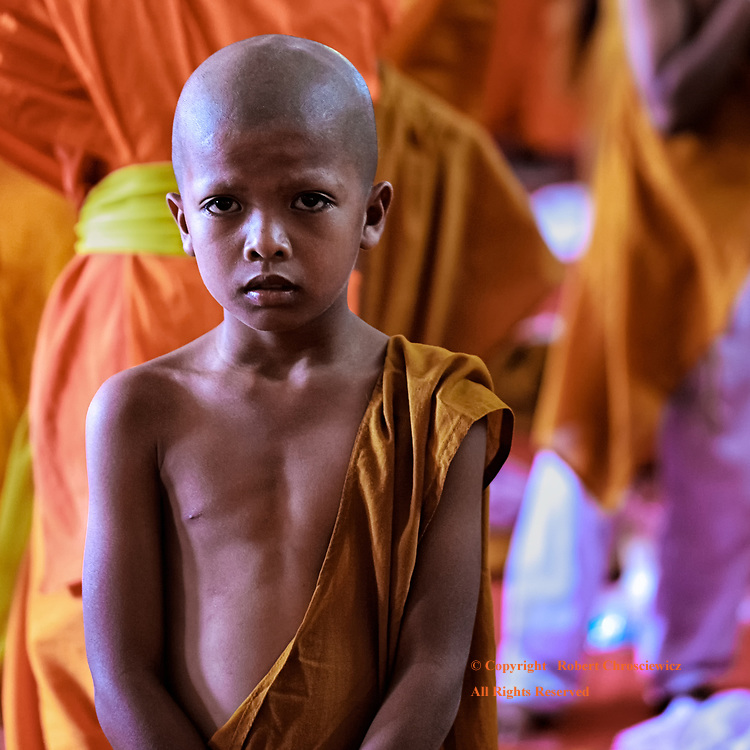 New Monk: A young boys kneel stands nervously, wearing new saffron robes as he starts the ordination ceremony to become a novice monk, Phra Mahathat Wat Nong Wang, Khon Kaen Thailand.