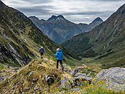Descending from the moraine lip of Crucible Lake, a side trip from the Gillespie Pass Circuit in Mount Aspiring National Park, in the Southern Alps. Makarora, Otago region, South Island of New Zealand. UNESCO lists Mount Aspiring as part of Wahipounamu - South West New Zealand World Heritage Area.