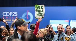 """11 December 2019, Madrid, Spain: """"We will rise"""" reads a sign, as hundreds of civil society and other actors hold an unauthorized protest outside the plenary hall of COP25 in Madrid, to draw attention to the failures of the climate talks and to call on rich countries to step up and pay up for real solutions, and to highlight the threat of loopholes, false solutions like carbon markets, and the need for those who caused the climate crisis to pay up for loss and damage while respecting human rights."""