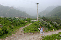 A woman carries a bundle of firewood on the border between Hebei and Liaoning provinces, China.