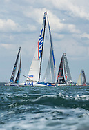 A cluster of french IMOCA 60 yacht's at the start of the 90th anniversary Rolex Fastnet Race on the Solent. A record fleet of 370 yachts will compete to win the Fastnet Challenge Cup.<br /> The 600 nautical mile race starts in Cowes, Isle of Wight, heading to the Fastnet Rock off the south west coast of Ireland and finishes in Plymouth.<br /> It is the world's biggest offshore race with 75% amateur sailors and professional yachtsmen competing against each other. <br /> Picture date Sunday 16th August, 2015.<br /> Picture by Christopher Ison. Contact +447544 044177 chris@christopherison.com