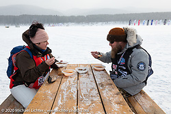 Grim Parts Co's Cathy and Sean Jordan of Utah, the leads on tech inspections and course starters, taking a break at the Baikal Mile Ice Speed Festival. Maksimiha, Siberia, Russia. Thursday, February 27, 2020. Photography ©2020 Michael Lichter.