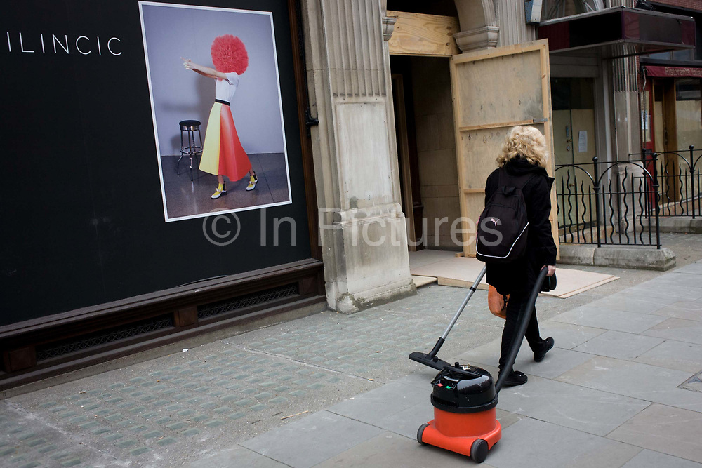Woman cleaner pulling a vacuum hover behind her, walks past a fashion poster in central London. Roksanda Ilincic—the British designer known for her colourful, feminine wares with a sculptural twist—revealed today that, early next year, she'll bow her first store at 9 Mount Street. Having studied Architecture and Applied Arts at university in Belgrade, her designs are soon to fill finished windows in Mayfair, central London.
