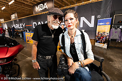 Willie G Davidson with a MDA's National Ambassador Tana Zwart of Sioux Falls, SD in the Harley-Davidson Garage at the Full Throttle Saloon during the Sturgis Black Hills Motorcycle Rally. Sturgis, SD, USA. Monday, August 5, 2019. Photography ©2019 Michael Lichter.