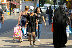 © Licensed to London News Pictures. 20/07/2021. London. UK. A shopper wearing a face covering in Tottenham, north London on the day after Freedom Day. Face coverings are no longer a legal requirement, but the government expects and has recommended that people should continue to wear face coverings whilst shopping and in crowded areas, such as public transport. Photo credit: Dinendra Haria/LNP