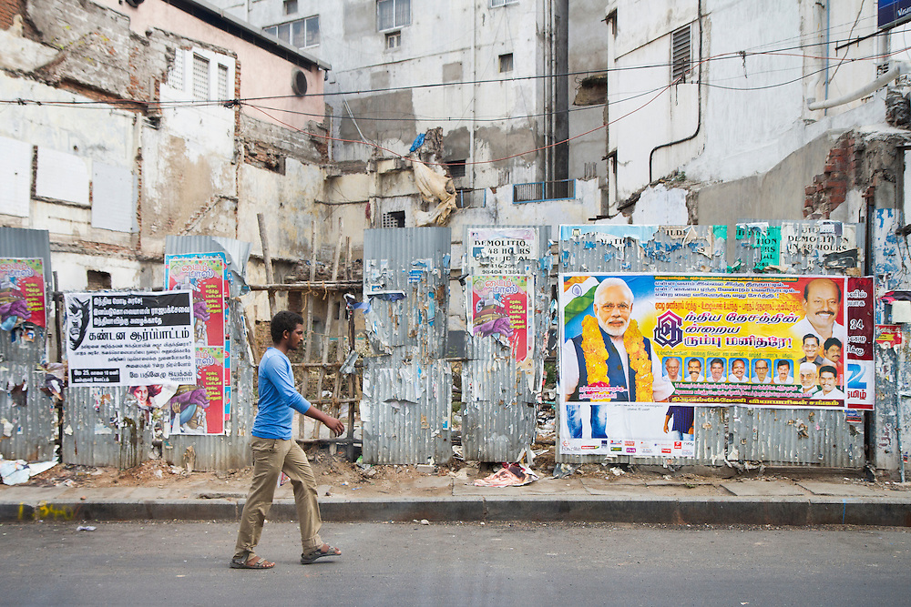 A man walks by a poster featuring India's newly elected Prime Minister Narendra Modi in the streets of Chennai, India.