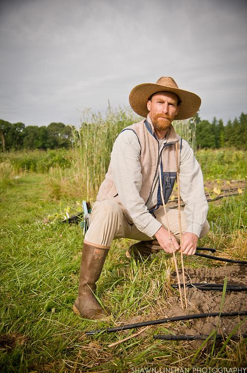 Josh Volk works on the irrigation system at Slow Hand Farm.