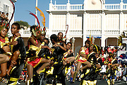 Dancers from one of the collectivities that dispute Mindelos Carnival prize performing during the parade in Lisboa street on Carnival Tuesday. On the background the facade of ancient Portuguese Governor house that works as the Court nowadays.