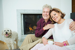 Portrait of senior couple with dog sitting in front of fireplace, smiling
